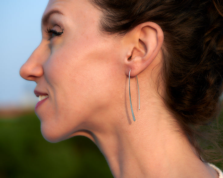 Silver open hoop earrings being worn by a woman