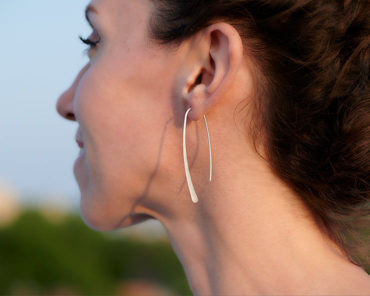 Open hoop dangle earrings being worn by a woman
