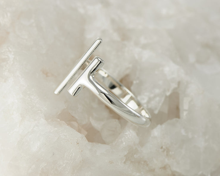 Silver parallel bars ring on white rock
