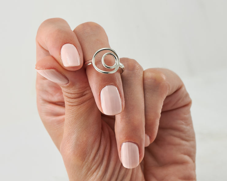 woman holding silver circles ring