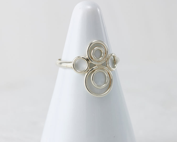 White ring holder with many circles Silver ring