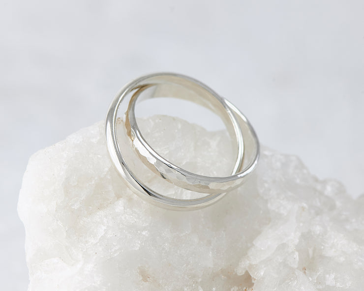 Silver interlocking russian wedding rings on white rock