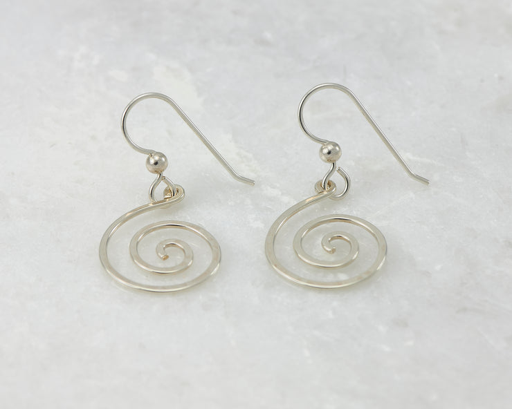 silver spiral earrings on white marble
