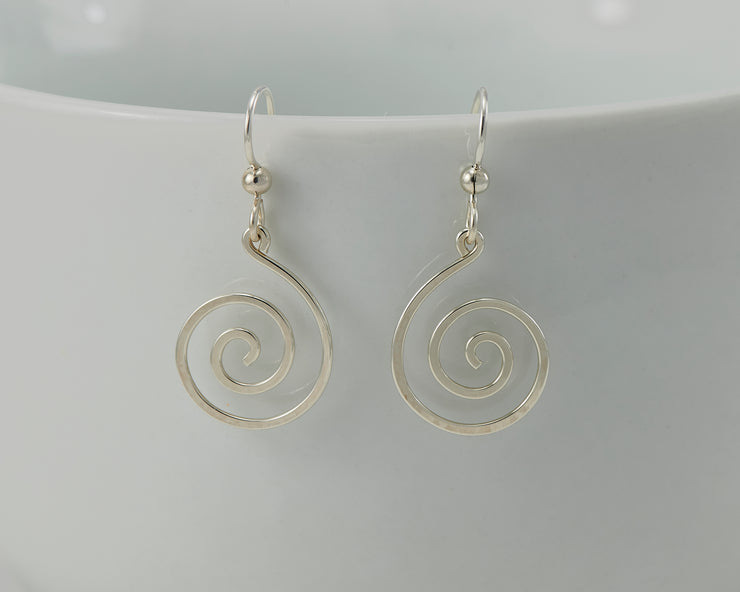 silver spiral earrings on white cup