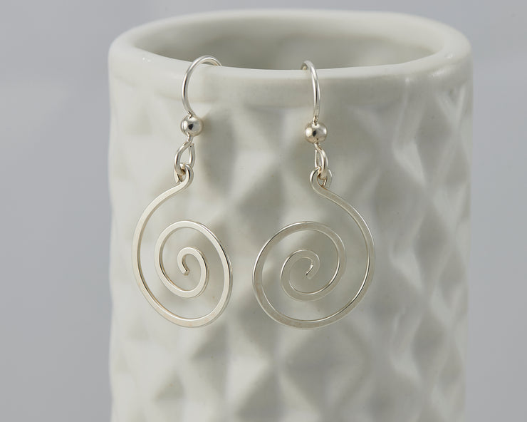 silver spiral earrings on geometric vase