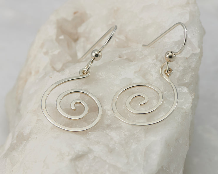 Silver dangle spiral earrings on white rock