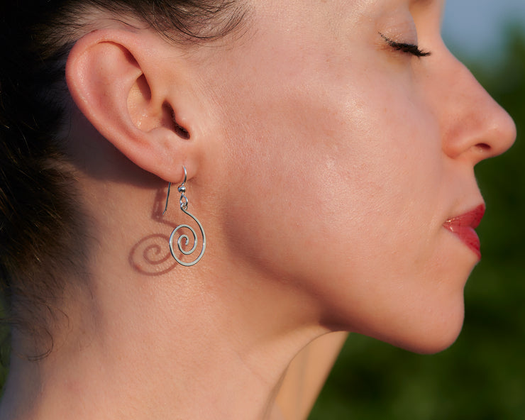 woman wearing silver spiral earrings facing out