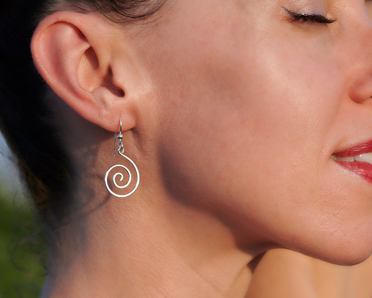 woman wearing silver spiral earrings