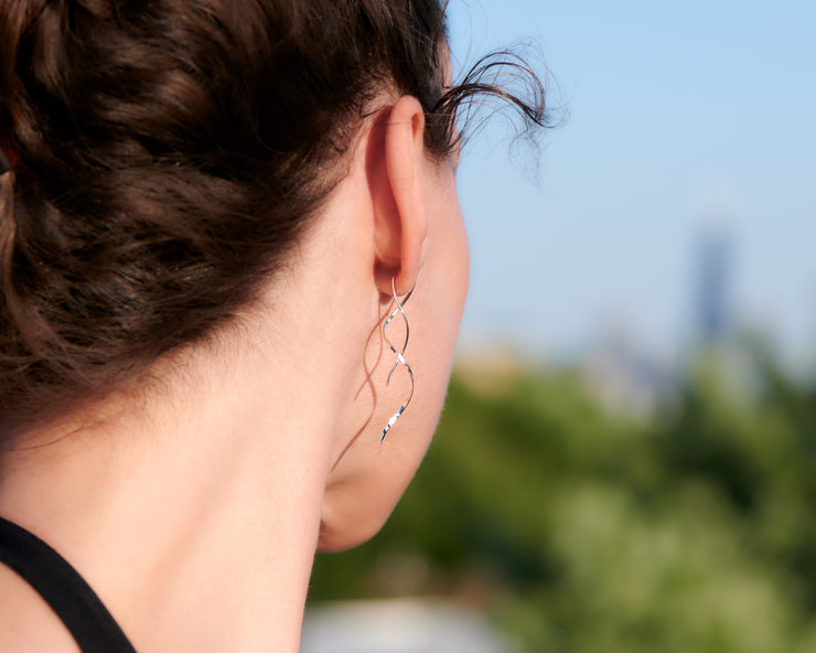 close up of woman wearing silver spiral threader earrings