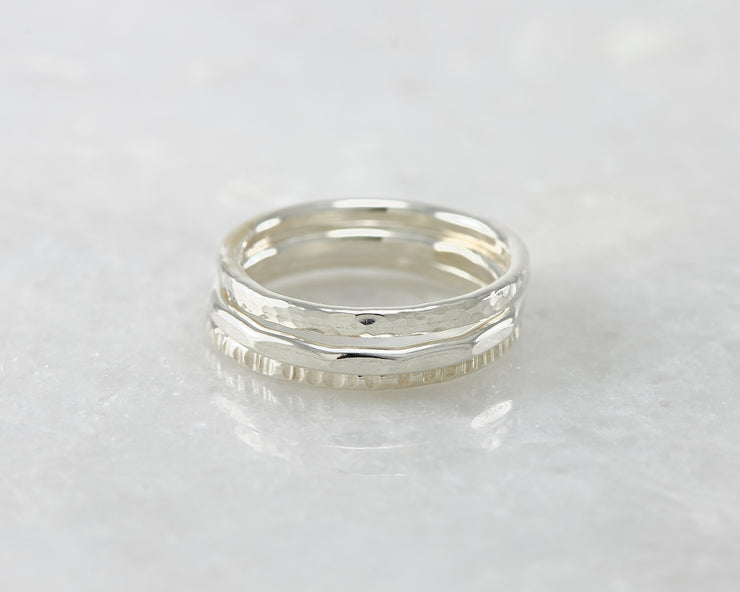 hammered stacking rings on white marble