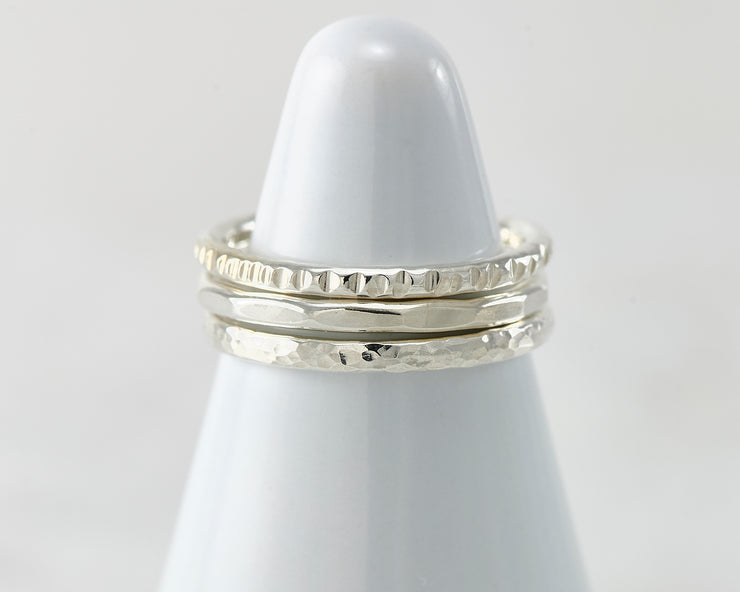 White rings holder with hammered Silver stacking rings