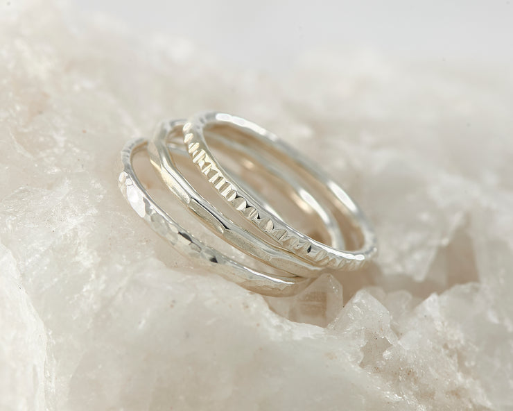 Silver hammered stacking rings on white rock
