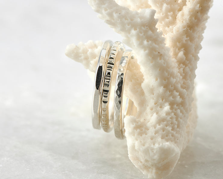 Silver hammered stacking rings on coral