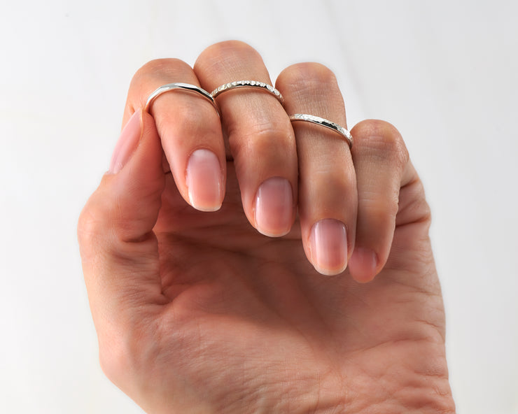woman wearing 3 silver stacking rings of different finishes