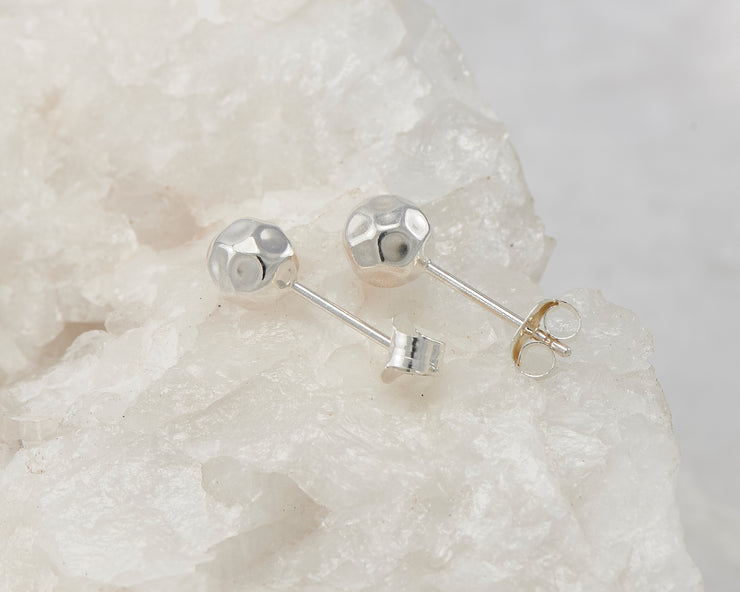 Silver stud ball earrings on white rock