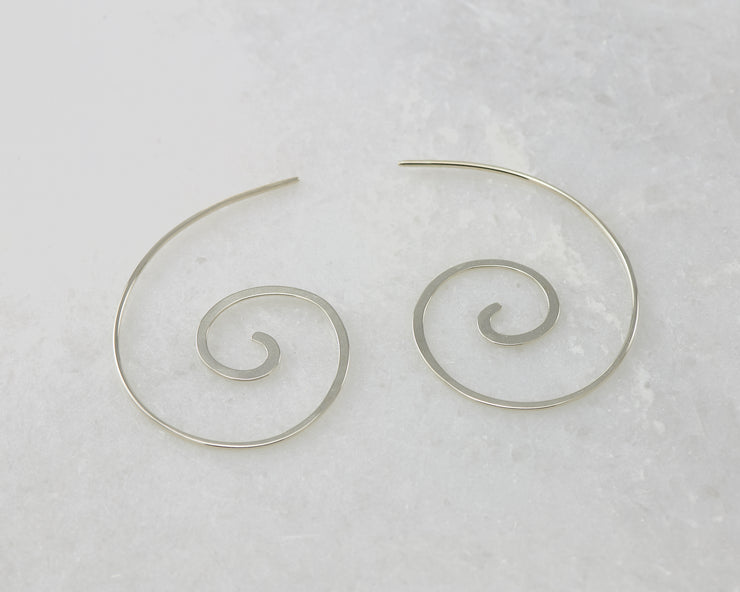 silver swirl threader earrings on white marble