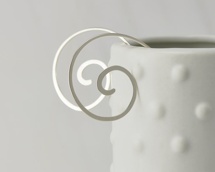 silver swirl threader earrings on dotted vase
