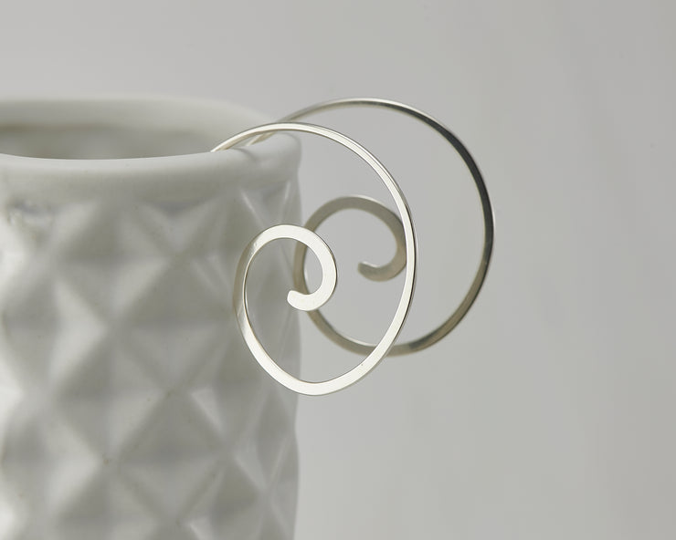 silver swirl threader earrings on geometric vase