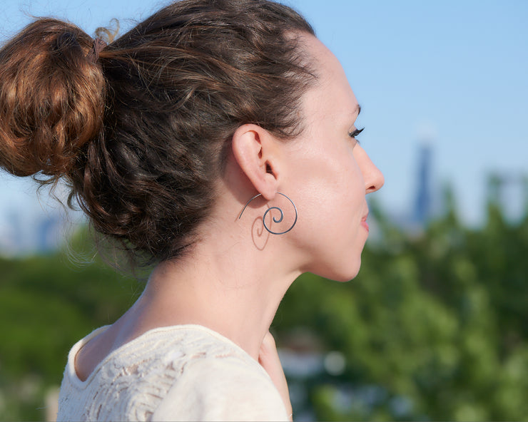 woman wearing silver swirl threader earrings