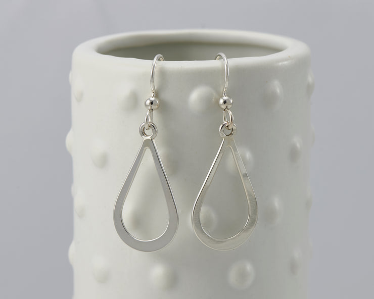 Silver teardrops earrings on dotted vase