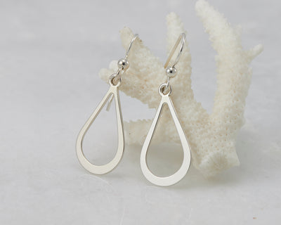 Silver teardrops earrings on coral