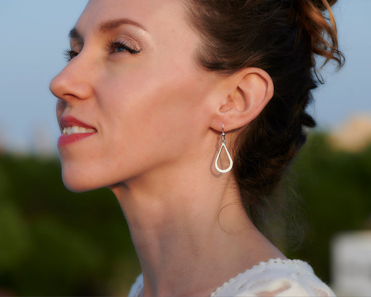 Woman wearing silver teardrops earrings