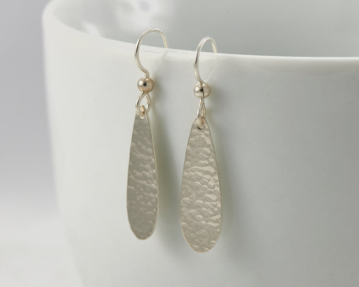 Silver teardrops earrings on white cup