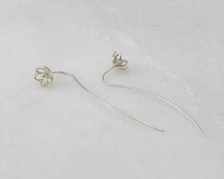 silver threader earrings on white marble