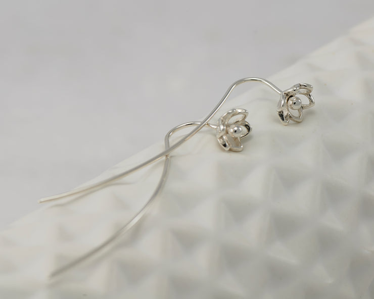 silver threader earrings on geometric vase