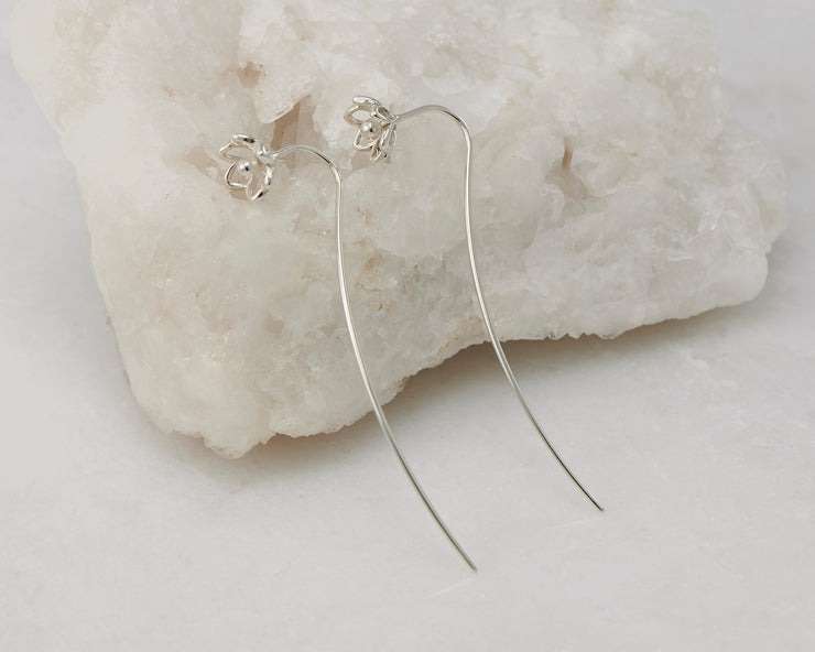 Silver dangle threader earrings on white rock
