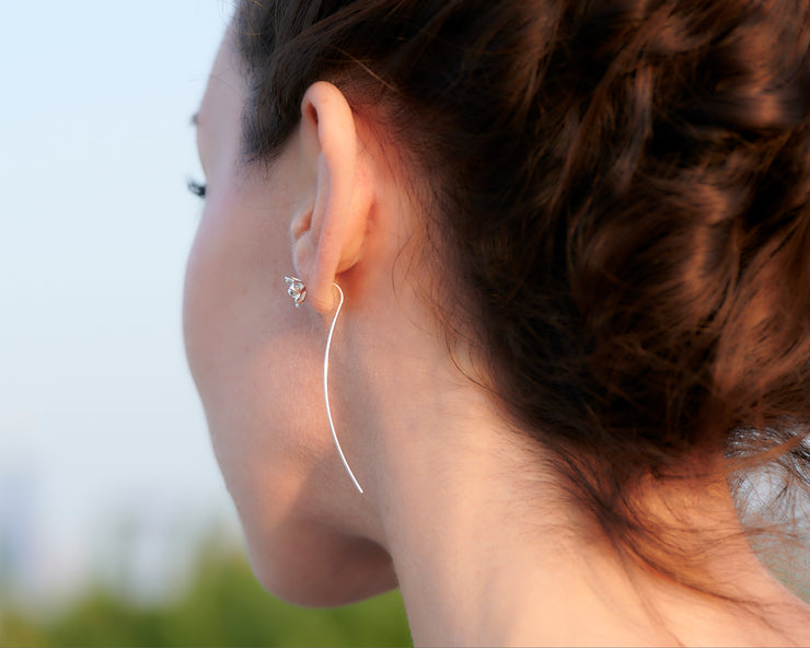 woman facing forward wearing silver threader earrings