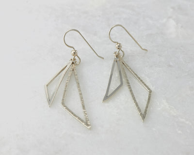 Silver polished triangle earrings on white marble
