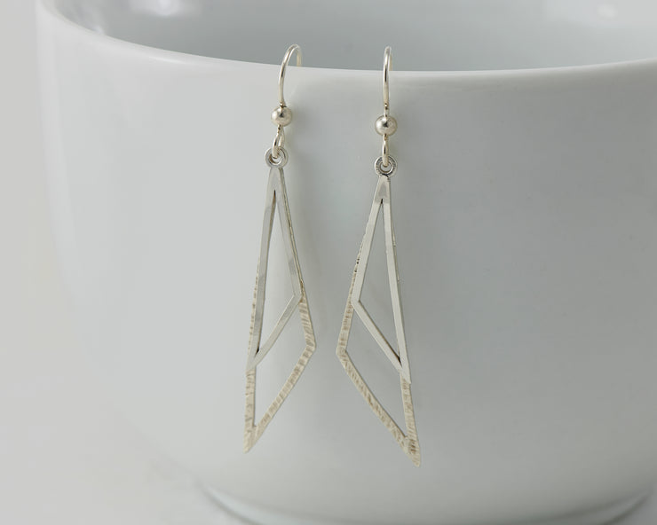 Silver triangle earrings on white cup