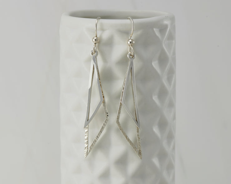 Silver triangle earrings on geometric vase