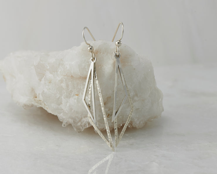 Silver triangle earrings on white rock