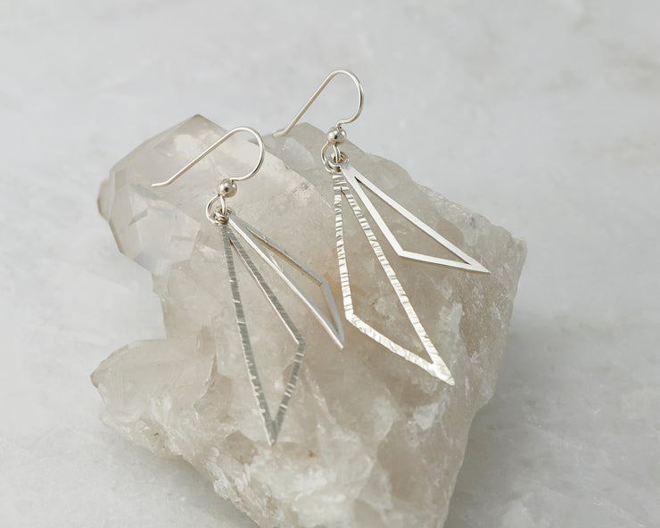 Silver triangle earrings on crystal rock