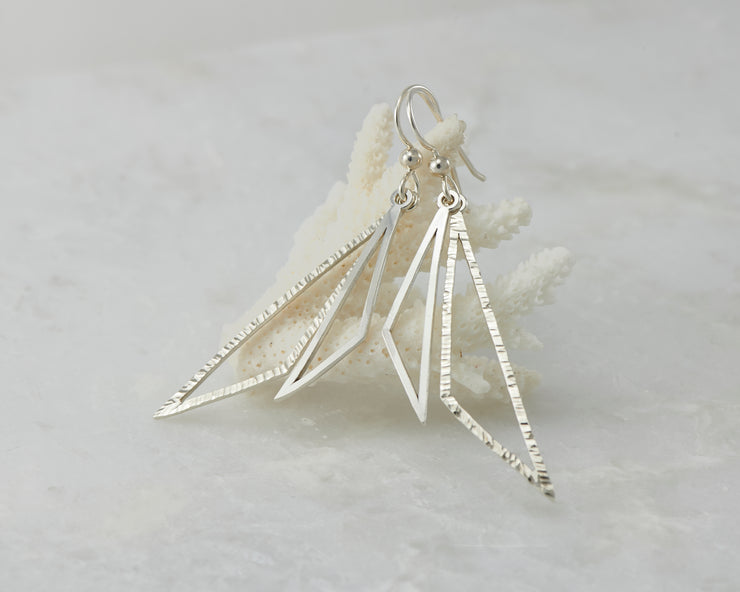 Silver triangle earrings on coral