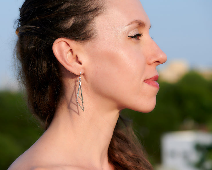 Woman wearing silver triangle earrings