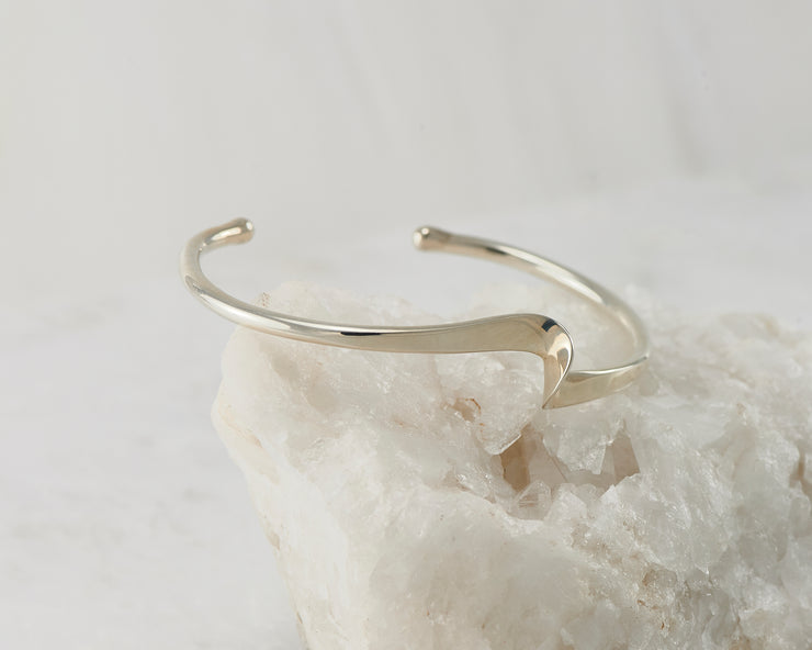 Silver wave cuff bracelet on white rock
