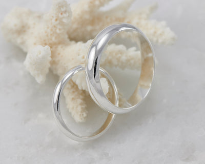 his and hers silver wedding band set on coral