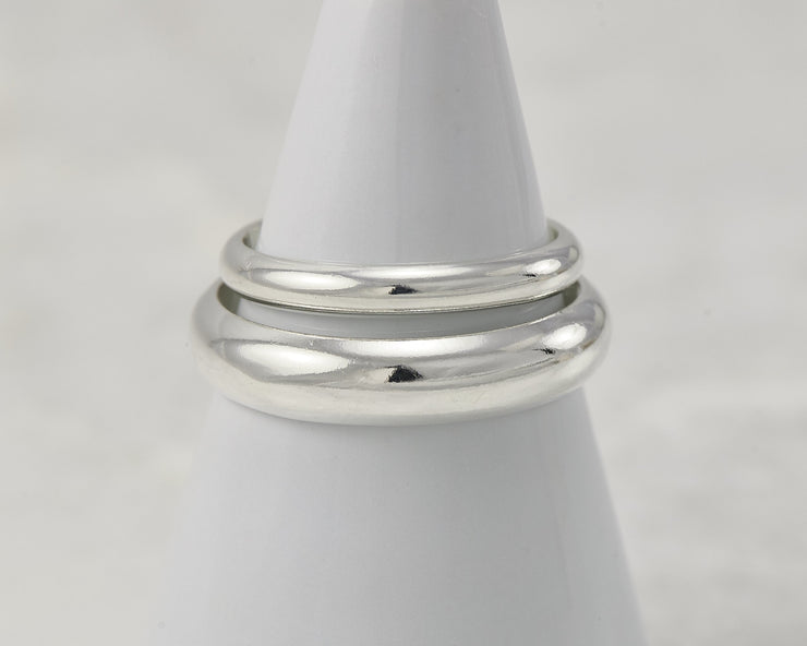 two silver polished wedding rings on white ring holder
