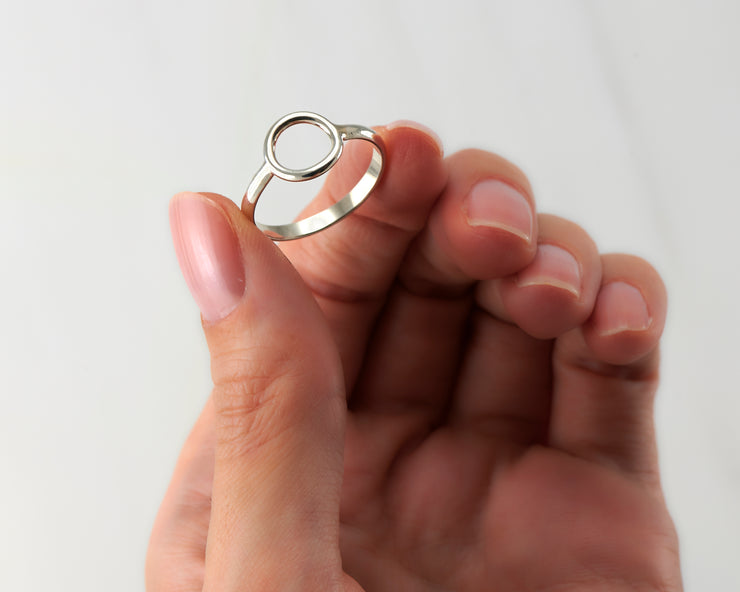 woman holding silver circle ring