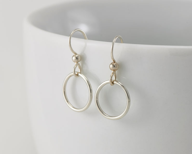 silver small hoop earrings on white cup