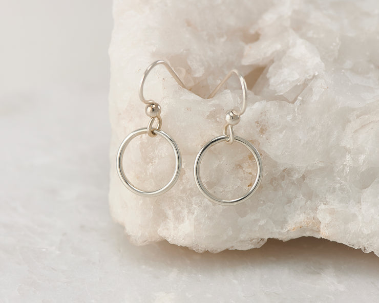 Silver dangle small hoop earrings on white rock