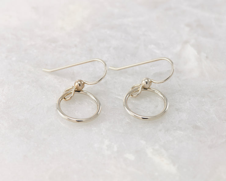 silver small hoop earrings on white marble