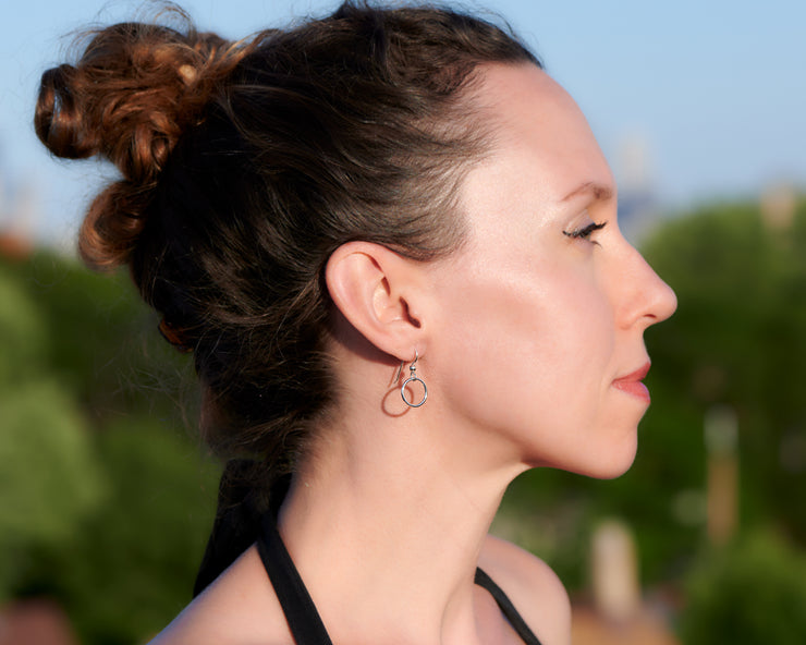 woman wearing silver small hoop earrings