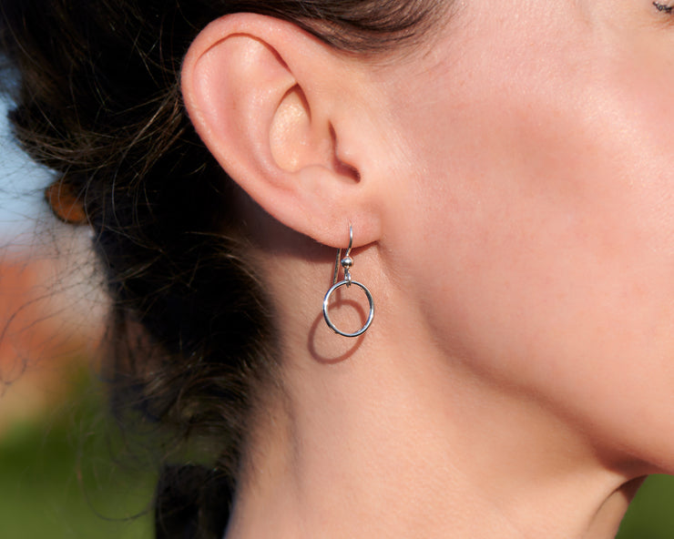 close up of woman wearing silver small hoop earrings