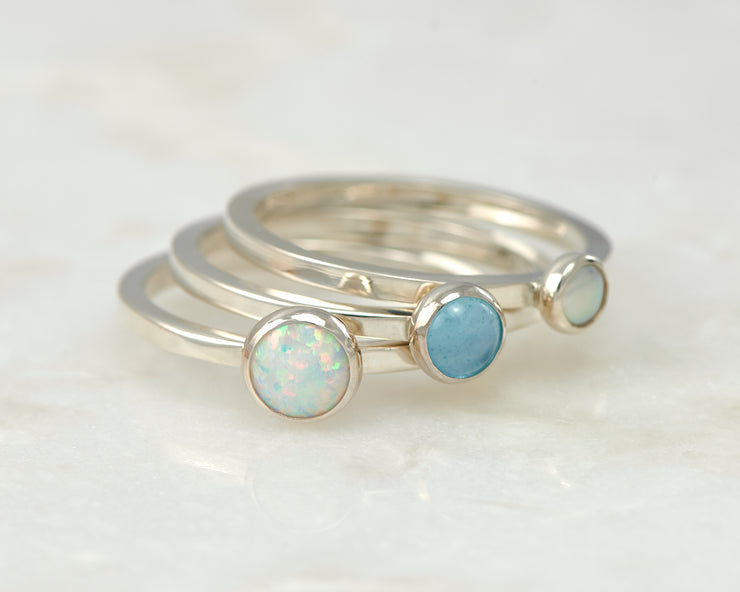simple opal, pearl, blue topaz silver stacking rings on white marble