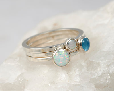 silver stacking rings opal, pearl, blue topaz on white rock