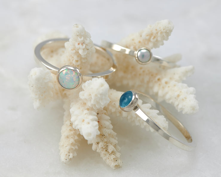 opal, pearl, blue topaz ring on coral